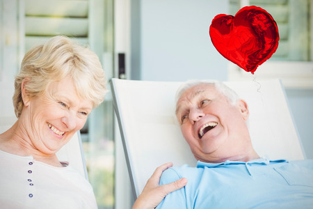 sacar la lengua: Red heart balloon against happy senior couple relaxing on lounge chair 3d Foto de archivo