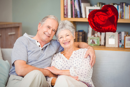 Red heart balloon against portrait of happy senior couple sitting on sofa 3d
