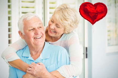 Red heart balloon against happy senior couple embracing 3d
