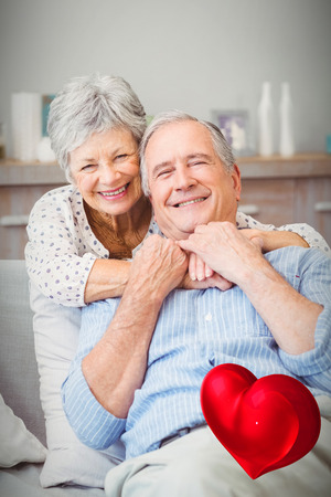 red heart against portrait of smiling senior couple embracing 3d