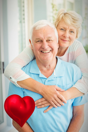 red heart against portrait of happy senior couple at home 3d