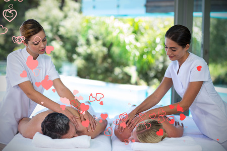 Valentines heart design against young couple receiving a back massage from masseur 3d