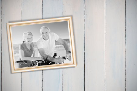 Wooden planks against portrait of retired couple with their bikes photo