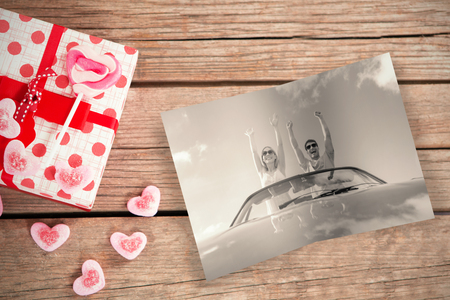 valentine gift against crazy couple standing in red cabriolet