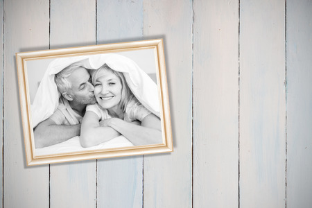 Closeup of mature man kissing womans cheek in bed against wooden planks photo