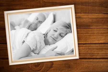 Overhead of wooden planks against mature couple sleeping with eyes closed in bed photo