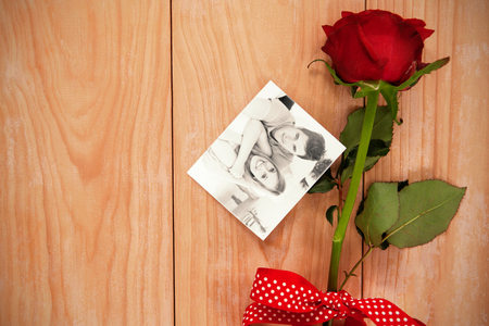 Smiling beatiful couple sitting on a sofa against red heart envelope and a red rose photo