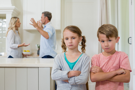 Sad sibling standing with arms crossed while parents arguing each other at home Stock Photo