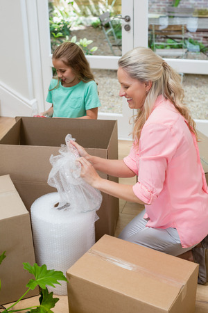 Mother and daughter unpacking carton boxes in living room at new home