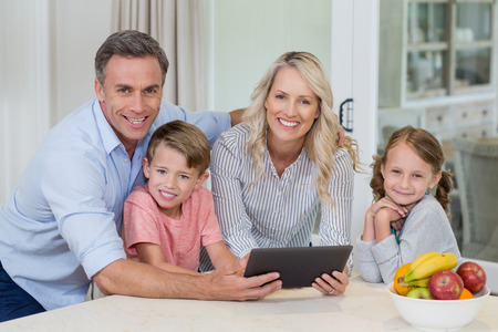 Portrait of happy family using digital tablet in kitchen at home