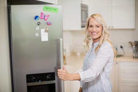 Retrato de la mujer hermosa puerta de refrigerador de la fregona en la cocina en el hogar Foto de archivo - 71189868