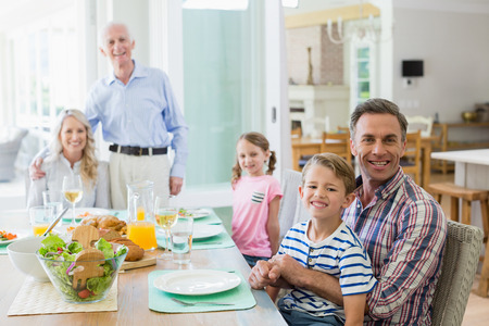 Portrait of happy multi- generation family having meal on dinning table at home