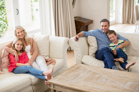 changing channel: Parents and kids watching tv in living room at home Stock Photo