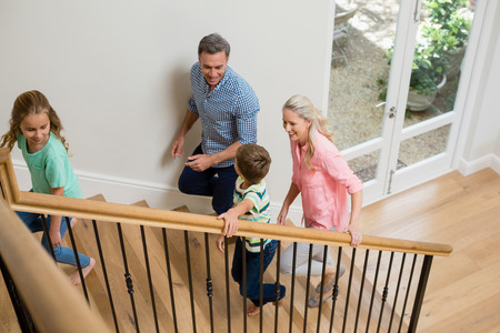upstairs: Smiling parents and kids walking upstairs at home Stock Photo