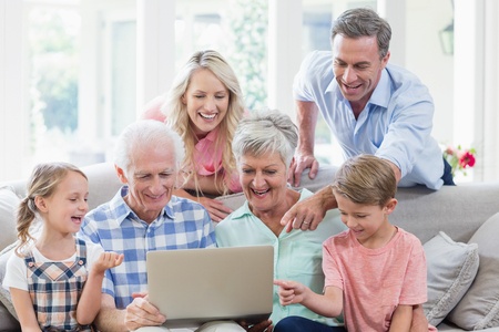 family  room: Happy multi-generation family using laptop in living room at home