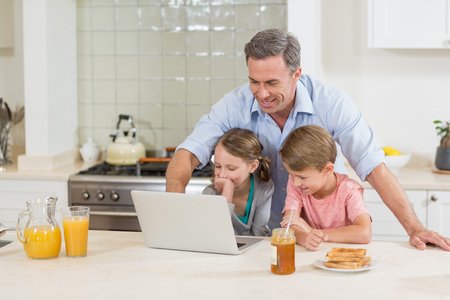 Father and his kids using laptop while having breakfast in kitchen Imagens