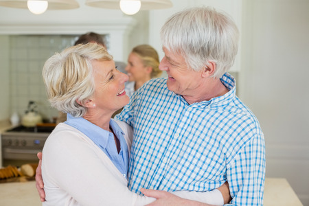 Romantic senior couple looking face to face in kitchen at home Stock Photo