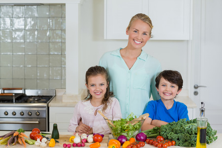 Portrait of mother and kids smiling in kitchen at home Stock Photo