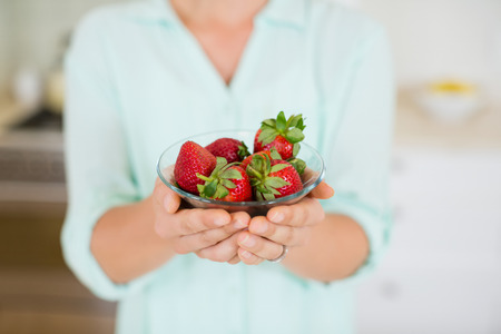 Mid section of beautiful woman holding glass of strawberry in kitchen at home Stock Photo