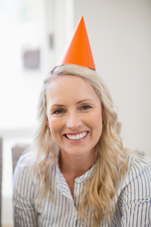 Smiling beautiful woman with party hat at home