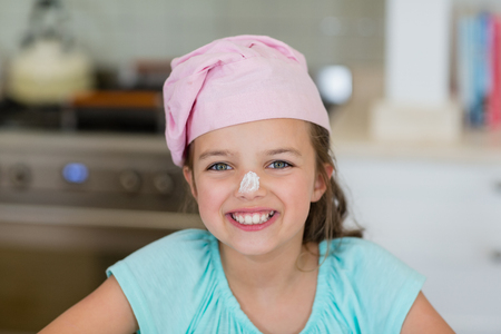 Portrait of smiling girl with flour on nose in kitchen Stock Photo