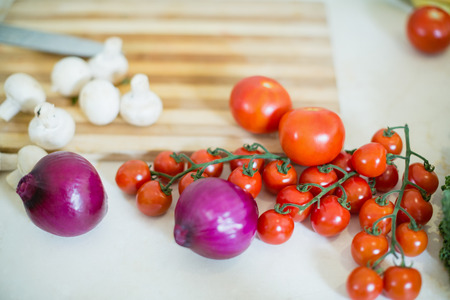 Cherry tomato, onion and mushroom on kitchen worktop at home