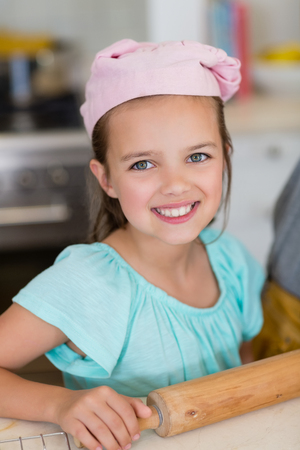 ageing process: Portrait of smiling girl wearing chefs hat with rolling pin in kitchen at home