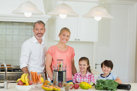 Portrait of happy parents and their two kids standing in kitchen at home Stock Photo