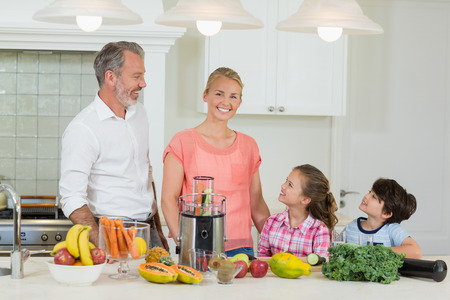 Parents interacting with their kids in kitchen at home Stock Photo