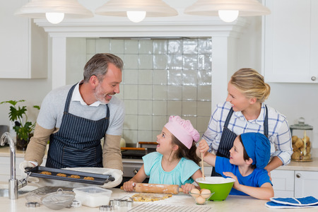 ageing process: Happy parents and kids preparing food in kitchen at home