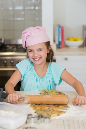 Portrait of smiling girl sheeting the dough with a rolling pin in the kitchen at home
