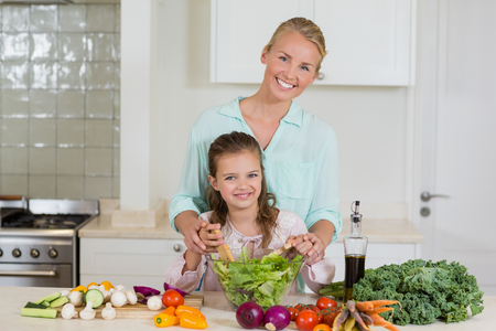 Mother and daughter preparing salad in kitchen at home Stock Photo