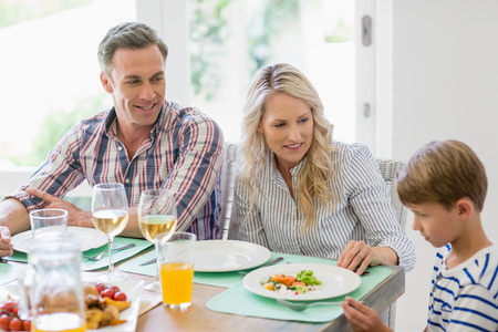 Parents interacting with son on dining table at home