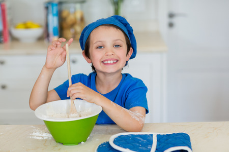 Portrait of smiling boy mixing cookie dough in kitchen at home Stock Photo