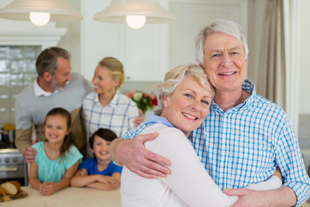 ageing process: Portrait of happy senior couple embracing each other in kitchen and family standing in background