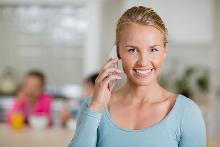 house call: Smiling woman talking on mobile phone in kitchen at home