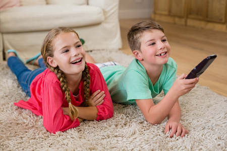 Siblings lying on rug and watching television in living room at home Stock Photo