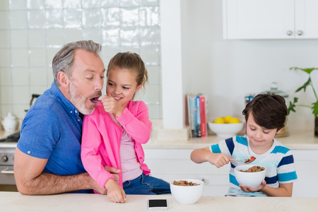 Father and kids having breakfast in kitchen at home Stock Photo