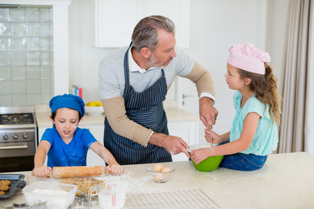 ageing process: Father and kids preparing food in kitchen at home
