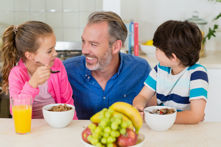 Smiling father and kids having breakfast in kitchen at home