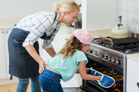 ageing process: Mother and daughter placing tray of cookies in oven at kitchen