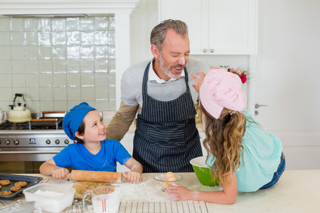 domicile: Happy father and kids having fun while making dough in kitchen at home Stock Photo