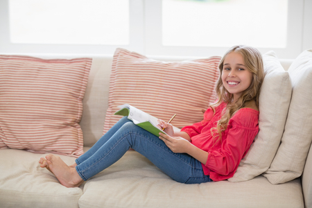 Portrait of smiling girl sitting on sofa and doing homework in living room at home