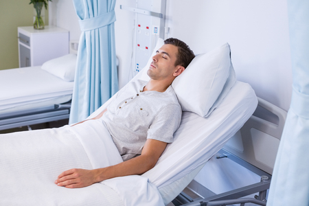 Male patient sleeping on bed in hospital Stock Photo