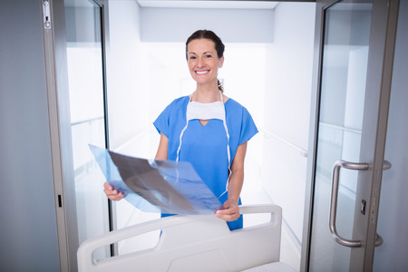 Portrait of smiling doctor standing with x-ray report in hospital Stock Photo
