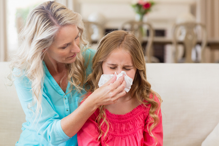 Mother helping daughter blowing her nose on sofa in living room at home Stock Photo