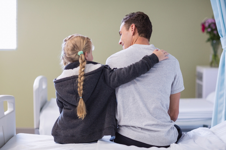 Rear view of daughter comforting her sick father in hospital room Stock Photo
