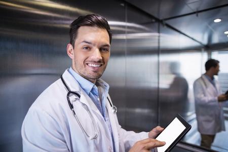 Portrait of smiling doctor using digital tablet in corridor at hospital