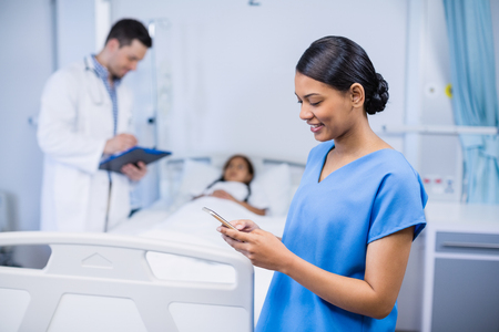 Smiling nurse using mobile phone in hospital room