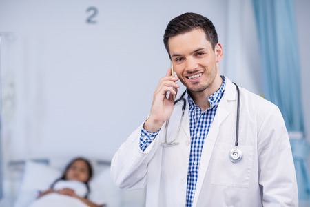 Portrait of smiling doctor talking on mobile phone in hospital room Stock Photo